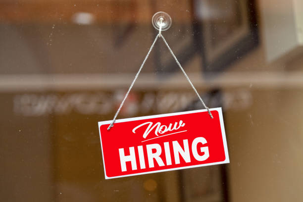 """Red sign hanging at the glass door of a shop saying: """"Now hiring""""."""